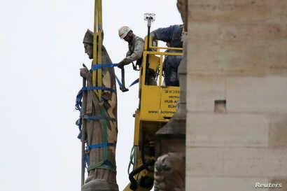 Men work on a statue on a facade at Notre-Dame Cathedral after a massive fire devastated large parts of the gothic structure in Paris, France, April 16, 2019.