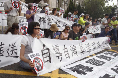 """FILE - Protesters of same-sex marriage hold banners and signs reading, """"Same-sex marriage is unwelcome in Taiwan"""" after Taiwan's Constitutional Court ruled in favor of same-sex marriage on Wednesday outside of the Legislative Yuan in Taipei, Taiwan, ..."""