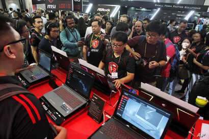 FILE - Visitors review new MSI computer products during 2018 Computex, in Taipei, Taiwan, June 5, 2018.