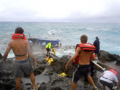 FILE - People clamber on Christmas Island during a rescue attempt as a boat breaks up in the background, Dec. 15, 2010. The boat, packed with dozens of asylum-seekers, smashed apart on cliff-side rocks in heavy seas, sending some to their deaths.