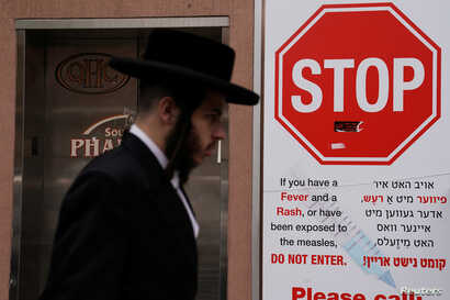 A man walks past a sign advising about a measles outbreak in the Brooklyn Borough of New York, New York, U.S., April 25, 2019.   REUTERS/Carlo Allegri - RC1E7FDD6400