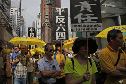 "Pro-democracy protesters carry placards with Chinese reads ""Vindicate June 4th"" during a demonstration in Hong Kong, May 26, 2019."