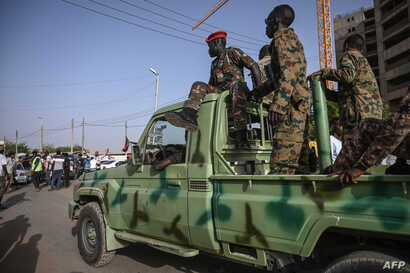 Members of the Sudanese military sit atop a pickup as protesters rally outside the army headquarters in the capital Khartoum, April 27, 2019.