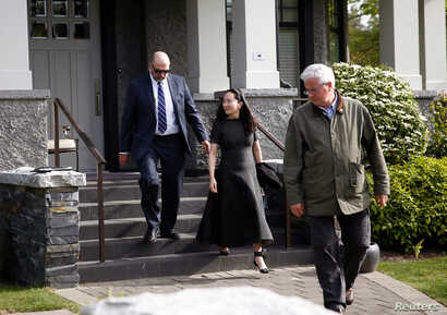 Huawei's Financial Chief Meng Wanzhou leaves her family home flanked by private security in Vancouver, British Columbia, Canada, May 8, 2019.