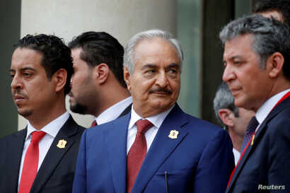 Khalifa Haftar, center, the military commander who dominates eastern Libya, leaves after an international conference on Libya at the Elysee Palace in Paris, May 29, 2018.