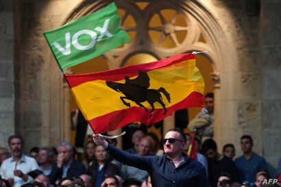 """FILE - A man waves a Spanish flag with the silhouette of the spanish medieval nobleman and military leader Rodrigo Diaz de Vivar """"El Cid"""", during a campaign rally of far-right party Vox, in Burgos, ahead of general elections."""