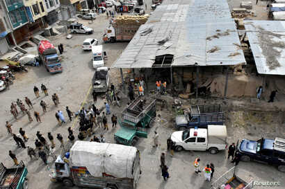 Rescue workers and army soldiers gather at the site of a blast at a vegetable market in Quetta, Pakistan, April 12, 2019.