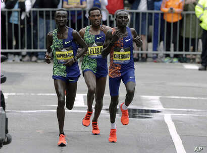 Kenneth Kipkemoi (L) of Kenya, Lelisa Desisa (C), of Ethiopia, and Lawrence Cherono (R), of Kenya, compete in the final mile of the 123rd Boston Marathon on April 15, 2019, in Boston.