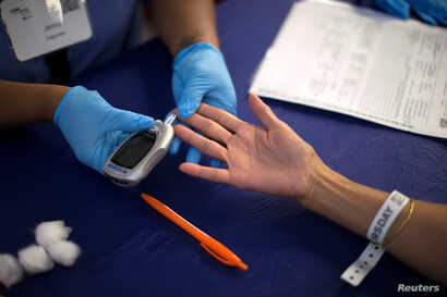 A person receives a test for diabetes during Care Harbor L.A. free medical clinic in Los Angeles, Sept. 11, 2014.