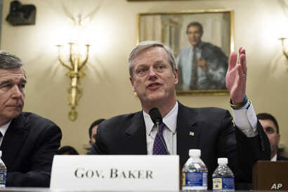 North Carolina Gov. Roy Cooper, left, watches as Massachusetts Gov. Charlie Baker speaks while they testify before the House Natural Resources Committee hearing on climate change, on Capitol Hill in Washington.