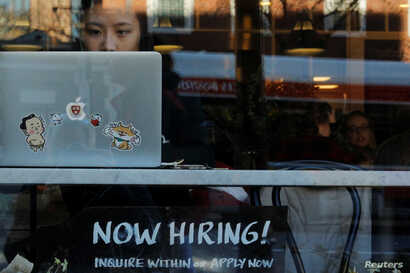 """FILE - A """"Now Hiring"""" sign sits in the window of a bakery-cafe in Cambridge, Massachusetts, Feb. 11, 2019."""