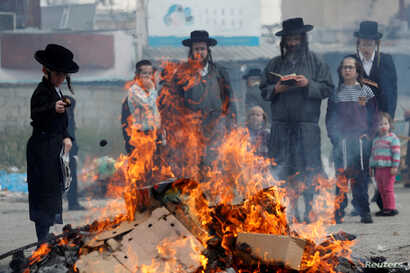 Ultra-Orthodox Jews burn leaven in the Mea Shearim neighborhood of Jerusalem ahead of the Jewish holiday of Passover, in Jerusalem, April 19, 2019.
