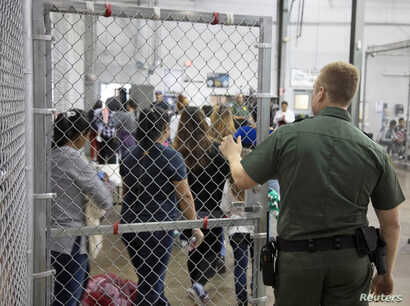 FILE - Detainees are seen inside fenced areas at Rio Grande Valley Centralized Processing Center in Rio Grande City, Texas, June 17, 2018.