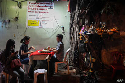 FILE - A fortune-teller, right, attends to a customer in Bangkok, Feb. 12, 2019.