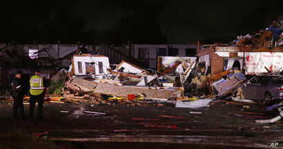 Police stand at the ruins of a hotel in El Reno, Okla., Sunday, May 26, 2019, following a likely tornado touchdown late Saturday night.