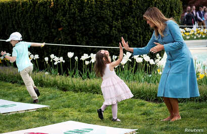 U.S. first lady Melania Trump high fives a child at the hopscotch station during the 2019 White House Easter Egg Roll on the South Lawn of the White House in Washington, U.S., April 22, 2019.