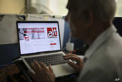 An Indian man browses through the twitter account of Alt News, a fact-checking website, in New Delhi, India, April 2, 2019.