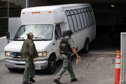FILE - A van carrying asylum-seekers from the border is escorted by security personnel as it arrives at immigration court, in San Diego, March 19, 2019.