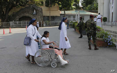 Sri Lankan Catholic nuns push a wheelchair carrying a survivor of the Easter attack for a holy mass held to bless the victims of the attacks in Colombo, Sri Lanka, May 11, 2019.