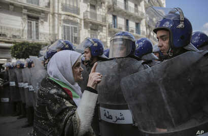 An elderly woman confronts security forces during an anti-government demonstration in Algiers, Algeria, April 10, 2019.