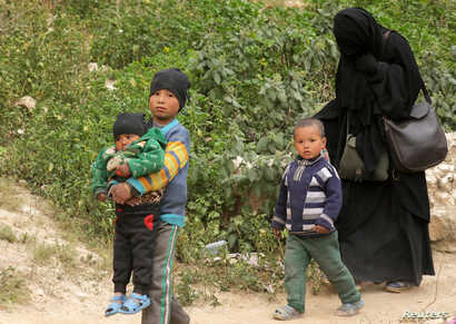 FILE - Woman and children of Islamic state militants walk as they surrendered in the village of Baghouz, Deir Al Zor province, Syria, March 14, 2019.