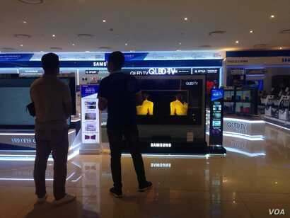 FILE - Shoppers check out smart TVs in Hanoi.