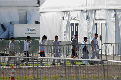 FILE - Children line up to enter a tent at the Homestead Temporary Shelter for Unaccompanied Children in Homestead, Fla., Feb. 19, 2019.