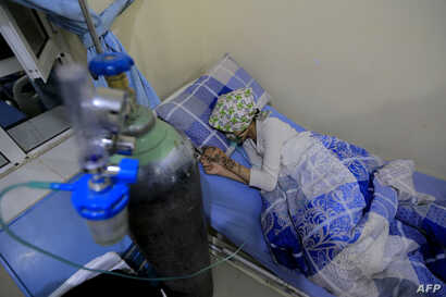 A wounded Yemeni schoolgirl lies on a bed as she receives treatment at a hospital in the capital Sanaa on April 7, 2019, following a blast that killed several civilians including students in Yemen's capital.