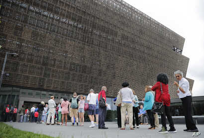 People wait in line to enter the Smithsonian National Museum of African American History and Cultural on the National Mall in Washington.