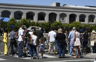 Neighbors and media members gather outside the Chabad of Poway synagogue, April 27, 2019, in Poway, Calif., after a shooting inside that resulted in at least one death.