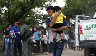 FILE - In this March 14, 2019, photo, Jose Fermin Gonzalez Cruz holds his son, William Josue Gonzales Garcia, 2, as they wait with other families who crossed the border near McAllen, Texas, for Border Patrol agents to check names and documents.