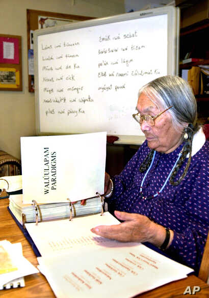 In this file photo, Umatilla elder, the late Cecilia Bearchum goes over a large binder used to teach Walla Walla, a critically endangered language spoken at the Umatilla Indian Reservation, Ore., March 6, 2002.  Ms. Bearcham passed away April 18, 201...