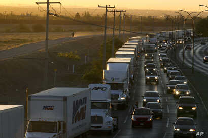 FILE- In this April 9, 2019, photo, trucks wait to cross the border with the U.S. in Ciudad Juarez, Mexico.  In a development that could compromise a major trade deal, President Donald Trump has said he is slapping a 5% tariff on all Mexican imports ...