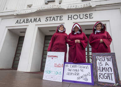 Bianca Cameron-Schwiesow, from left, Kari Crowe and Margeaux Hartline, dressed as handmaids, take part in a protest against HB314, the abortion ban bill, at the Alabama State House in Montgomery, Ala., on Wednesday April 17, 2019. (Mickey Welsh/The M...