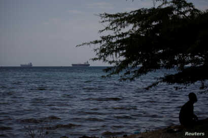 A man sits under a tree as two vessels are seen in the bay of Port-au-Prince, Haiti, April 12, 2019.