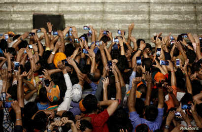 Supporters of Indian Prime Minister Narendra Modi use their mobile phones to take his picture as he addresses them after the election results at the Bharatiya Janata Party (BJP) headquarter in New Delhi, India, May 23, 2019.