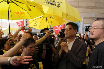 "Occupy Central pro-democracy movement founder Chan Kin-man (2nd R)  greets supporters as he arriving at the court for sentencing on his involvement in the Occupy Central, also known as ""Umbrella Movement"", in Hong Kong, Apr. 24, 2019."