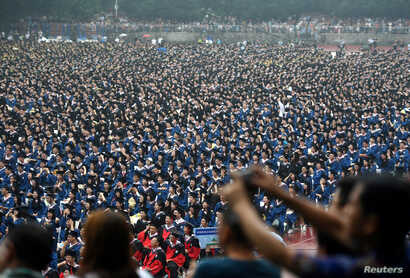 FILE - Students wearing academic gowns attend their graduation ceremony at Wuhan University in Hubei province, China, June 22, 2018.