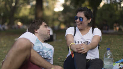 FILE - Tomas Ruiz talks with his friend Maria Julia Zuccotti as they hang out with friends at Las Heras Park in Buenos Aires, Argentina,  April 2, 2019, two days before he flew to Ireland in search of work.