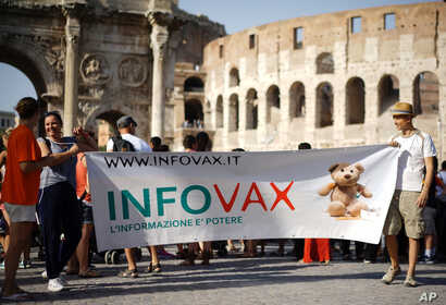 FILE - People rally for freedom of choice in deciding whether or not to vaccinate their children, in downtown Rome, Italy, July 22, 2017.