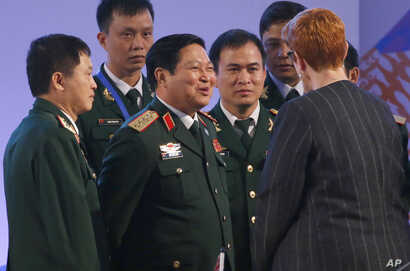 FILE - Vietnamese Defense Minister Gen. Ngo Xuan Lich, center, talks to then-Australian Defense Minister Marise Payne at the two-day ASEAN Defense Ministers Meeting, Oct. 24, 2017, north of Manila, Philippines.