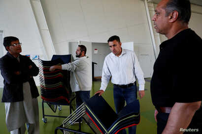 Sardar Faisal (2nd L) from Pakistan, a survivor of Christchurch shootings, helps to arrange chairs for a special prayers for the victims of the attacks in Christchurch, New Zealand, March 31, 2019.