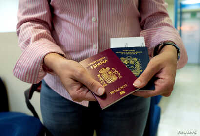 Mariana Elias, 27, shows her Venezuelan and Spanish passports at the Simon Bolivar International Airport, La Guaira, Venezuela, January 14, 2019. Before moving to Barcelona in January, Elias spent years in Caracas doing two degrees in chemical and pr...