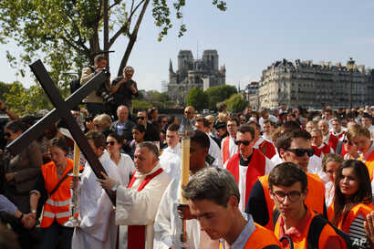 With the Notre Dame cathedral in background, religious officials carry the cross during the Good Friday procession, April 19, 2019, in Paris. French art conservation officials say the works inside Notre Dame suffered no major damage in this week's fi...