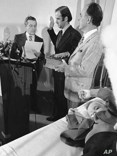 FILE - Four-year-old Beau Biden, foreground, plays near his father, Joe Biden, center, as he is sworn in as the U.S. senator from Delaware, by Senate Secretary Frank Valeo, left, in ceremonies in a Wilmington hospital, Jan. 5, 1973. Beau was injured ...