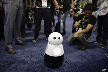 FILE - Mayfield Robotics' Kuri home robot is surrounded by attendees during CES Unveiled at CES International in Las Vegas, Jan. 7, 2018.