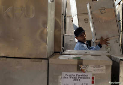 FILE - A worker unloads ballot boxes for the upcoming Indonesian presidential elections in Sidoarjo, near Surabaya, East Java, July 7, 2014.