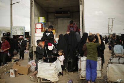 FILE - In this March 31, 2019, photo, women purchase goods from the back of a truck in the marketplace at al-Hol camp, near Hasakah, Syria. Al-Hol camp is home to tens of thousands of people who streamed out of the Islamic State group's last strong...