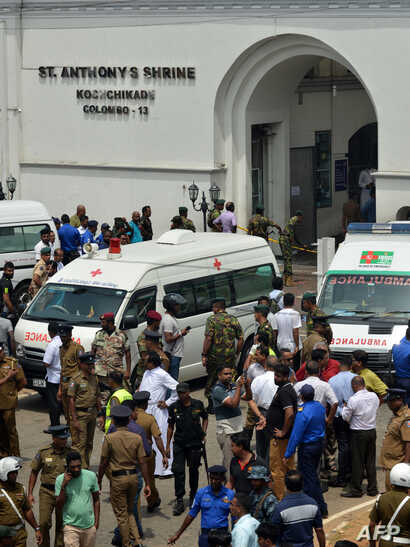 Ambulances are seen outside the church premises with gathered people and security personnel following a blast at the St. Anthony's Shrine in Kochchikade, Colombo, April 21, 2019.