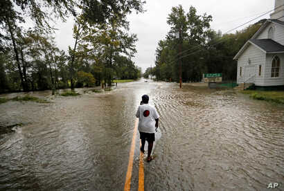Helen McKoy walks down a flooded street in her neighborhood as Florence continues to dump heavy rain in Fayetteville, N.C.,  Sept. 16, 2018.